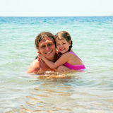 Father and baby daughter embracing and smiling in the sea Royalty Free Stock Images