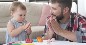 Father and daughter playing with plasticine. Father and baby daughter playing with plasticine at home stock video footage
