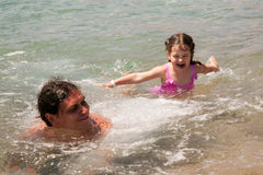 Father and baby daughter playing in the water. Royalty Free Stock Photography