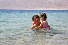 Father and baby daughter playing in the water. Stock Photo