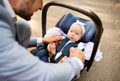Father with baby daughter sitting in car safety seat. Unrecognizable father outdoors with his cute baby daughter sitting in car safety seat Royalty Free Stock Photo