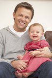 Father And Baby Daughter On Sofa. Portrait Of Father And Baby Daughter On Sofa Stock Photo