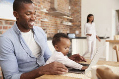 Father And Baby Daughter Use Laptop As Mother Prepares Meal Royalty Free Stock Image