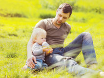 Father and baby drinks from a bottle sitting on grass. Summer Stock Photos