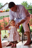 Father and baby girl in garden. Father supports his baby girl in her first steps  at home, outdoor in the garden Stock Photography
