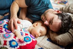 Father with a baby girl at home sleeping. Father with a baby girl at home, sleeping on the sofa. Paternity leave Royalty Free Stock Photography