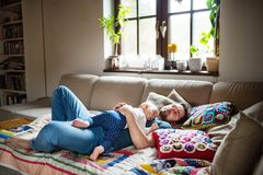 Father with a baby girl at home sleeping. Father with a baby girl at home, sleeping on the sofa. Paternity leave Stock Photo