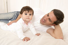Father and Baby Girl playing on bed Stock Photography