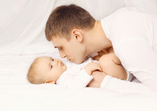 Father and baby at home lying on the bed together Royalty Free Stock Photos
