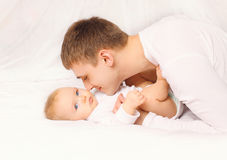 Father and baby at home lying on bed together bedtime Royalty Free Stock Images