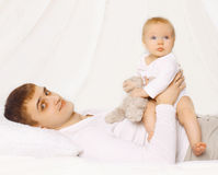 Father and baby at home lying on the bed together, child playing Stock Photography