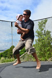 Father and baby Jumping on trampoline Royalty Free Stock Images