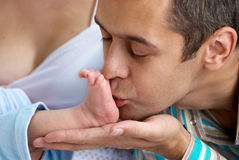 Father of baby kissing a leg Royalty Free Stock Photography