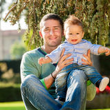Father and baby play on the grass stock photography