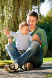 Father and baby play on the grass Stock Photos