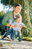 Father and baby play on the grass Royalty Free Stock Image