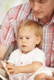Father and baby reading book. Father and baby sitting together and reading story book Stock Photography