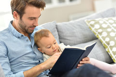Father and baby reading book at home Royalty Free Stock Photo