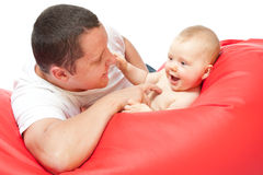 Father with baby on red sofa Stock Photos