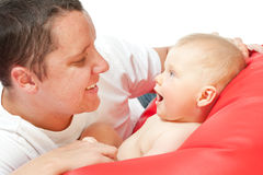 Father with baby on red sofa Royalty Free Stock Photos