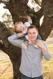 Father With Baby on Shoulders. Playing With Stick Royalty Free Stock Image