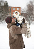Father and baby in snow. Father holding a baby up in the air, in a town with in fresh snow; playing and laughing Royalty Free Stock Photos