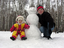 Father, baby, snowman royalty free stock images