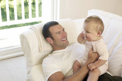 Father And Baby On Sofa. Happy young father with baby girl on sofa at home Royalty Free Stock Image