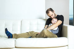 Father with baby on the sofa Stock Photography