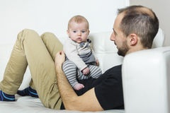 Father with baby on the sofa taking good time Stock Photography
