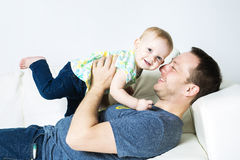 Father with baby on the sofa taking good time Stock Image