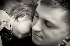 Father and baby son. Black and white closeup portrait of a young father with his baby son's head resting on his shoulder Royalty Free Stock Photos
