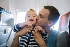 Dad kisses his son on the plane interior. Father and baby son during flight on airplane going on vacations. Dad kisses his son on the plane. Air travel with baby Stock Photography