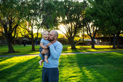 Father with baby son in green neighborhood Stock Photos