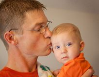 Father kissing his baby son. With blue eyes and blonde hair stock photo