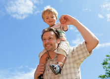 Father and baby son piggyback. Dad and his baby son playing piggyback with blue sky background Royalty Free Stock Images