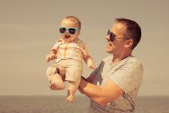 Father and baby son playing on the beach at the day time. People having fun outdoors. Concept of summer vacation and friendly family Royalty Free Stock Images