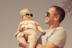 Father and baby son playing on the beach at the day time. People having fun outdoors. Concept of summer vacation and friendly family Stock Photography
