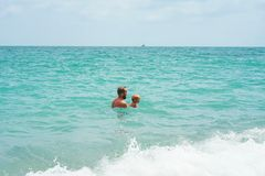 Father and son playing in the sea stock photography