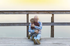 Father and baby son sitting on the wooden bridge. Father and baby son sitting on the wooden bridge near the river Stock Photo