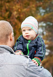 Father and baby son on walk. Baby on the shoulder of his father walking in the park autumn royalty free stock photography