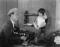 Father with baby in speaker horn of old radio Royalty Free Stock Image