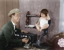 Father with baby in speaker horn of old radio Royalty Free Stock Photography