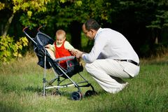 Father and baby in stroller Royalty Free Stock Images