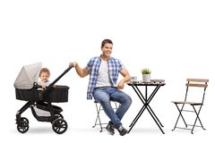 Father with a baby in a stroller sitting in a cafe. Isolated on white background royalty free stock photos