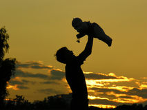 Father with baby on sunset. Shadowgraph; silhouette; shadow-figure royalty free stock photo