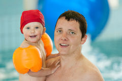 Father with baby in swimming pool are making fun. Baby and dad are swimming in swimming pool Royalty Free Stock Photos