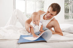 Father and baby together reading book Stock Photo