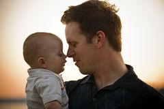 Father and Baby Touching Noses. At sunset. Horizontal Stock Photos
