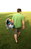Father with Baby in Tow. Isolated view of a man or father carrying a baby stock image